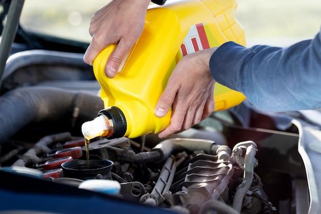 Equipaggi l'autista che versa e che rifornisce di carburante la qualità dell'olio nell'automobile del motore, primo piano.