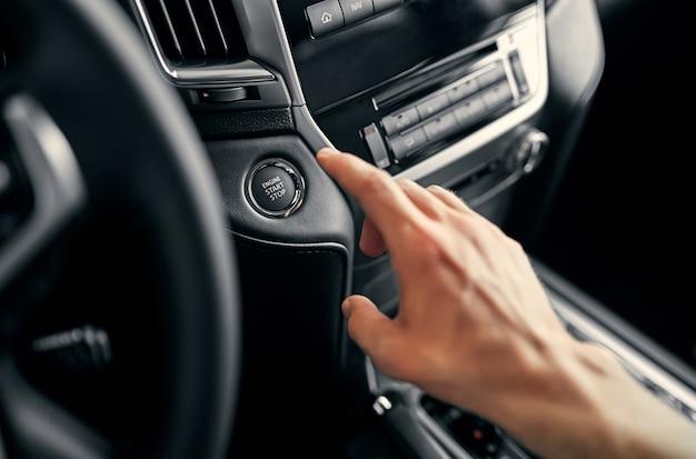 Driver dell'uomo che spinge un interruttore del pulsante di accensione di avviamento nella moderna auto di lusso.