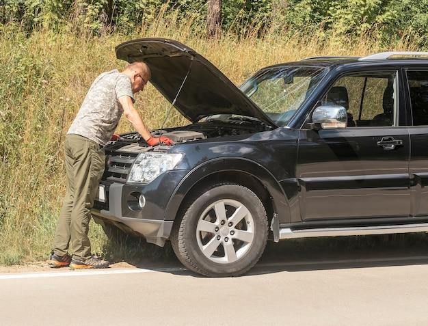 L'autista dell'uomo in piedi e guarda all'interno del cofano sollevato e pensa al problema dopo l'irruzione dell'auto ...