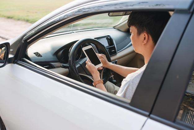 Autista uomo che usa lo smartphone in auto