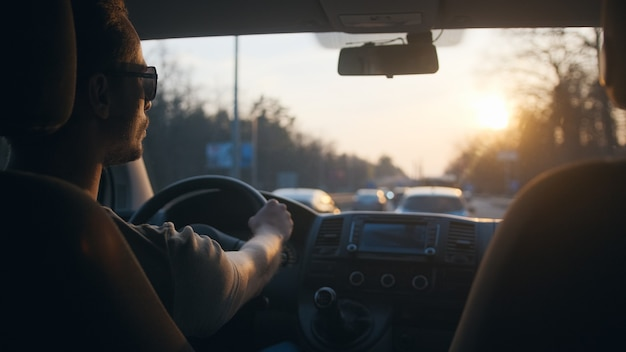 L'uomo guida l'auto in autostrada sullo sfondo del cielo al tramonto