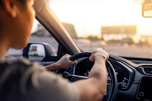 Uomo alla guida di un'auto lungo l'autostrada con il sole che splende nel parabrezza