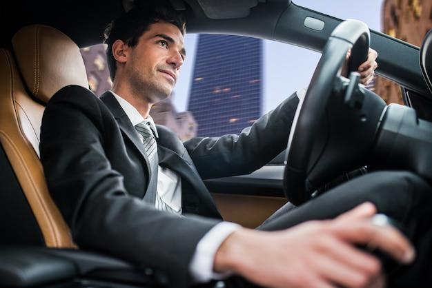 Uomo che guida auto in una città