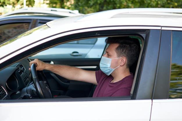 Un uomo alla guida di un'auto con una maschera medica durante l'epidemia di coronavirus