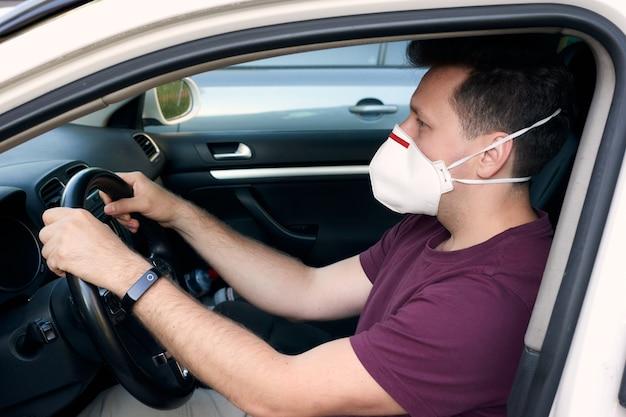 Un uomo alla guida di un'auto con una maschera medica durante un'epidemia