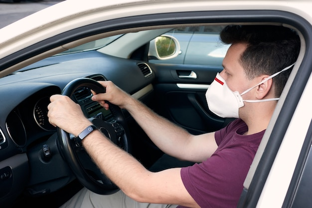 Un uomo alla guida di un'auto in un respiratore medico durante l'epidemia di coronavirus