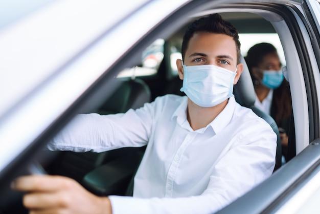 Uomo alla guida di un'auto con maschera protettiva durante la città di quarantena. covid 19.