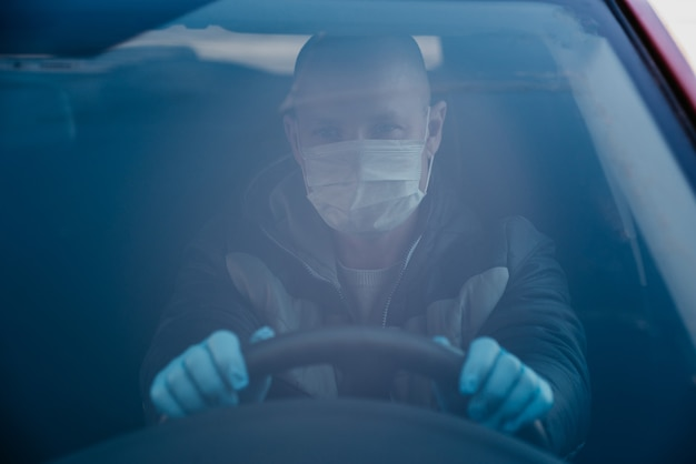 Uomo alla guida di auto in guanti e maschera medica protettiva. guida sicura in taxi durante la pandemia di coronavirus