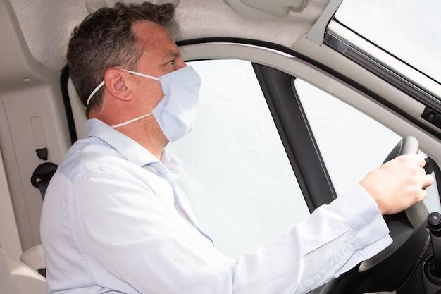 L'uomo alla guida di auto in maschera protettiva medica fatta a mano durante la coronavirus pandemica protegge conducente e passeggeri
