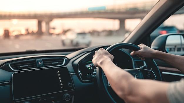 Uomo alla guida di un'auto sulla strada Foto Premium