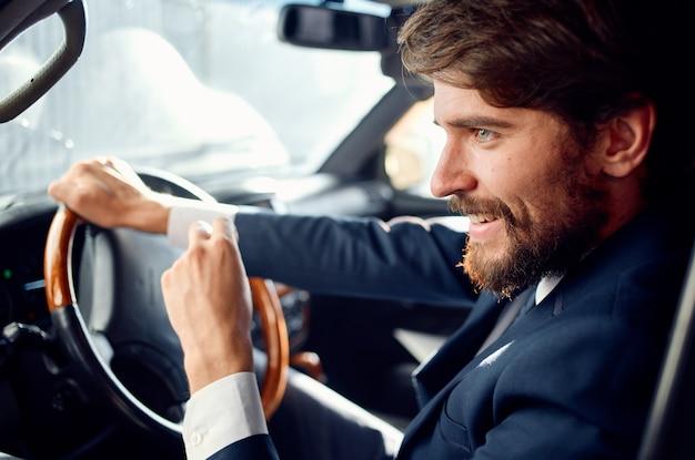 Uomo che guida una ricchezza ufficiale di viaggio in auto
