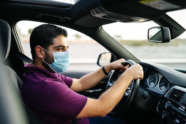 Uomo alla guida di un'auto che indossa una mascherina medica durante una pandemia di covid. concetto di coronavirus.