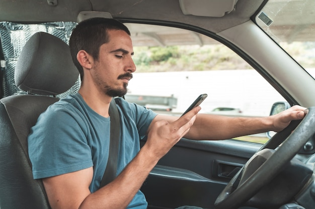 Uomo alla guida di un'auto mentre parla al telefono guida e invia sms a uno smartphone pericolo distrazione