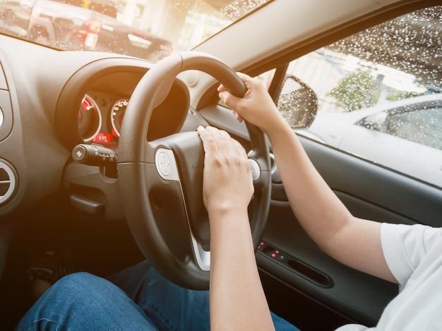 Uomo alla guida di auto con la mano sul clacson