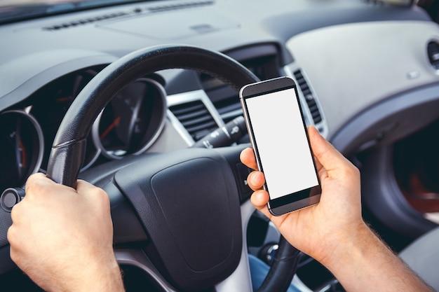 Uomo alla guida di un'auto con un telefono in mano. non scrivere e non guidare