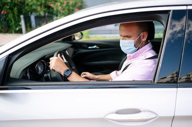 Uomo alla guida di auto con maschera protettiva