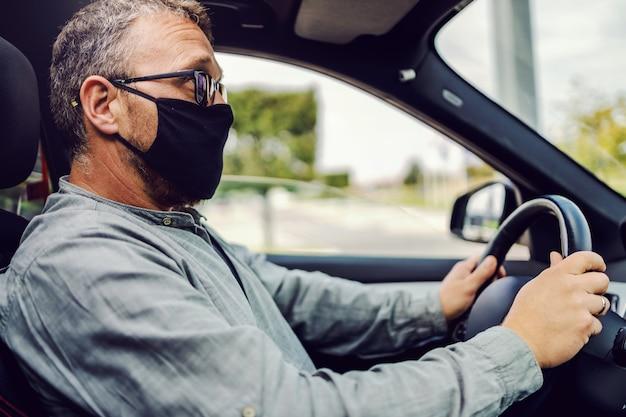 Uomo alla guida della sua auto durante il coronavirus.