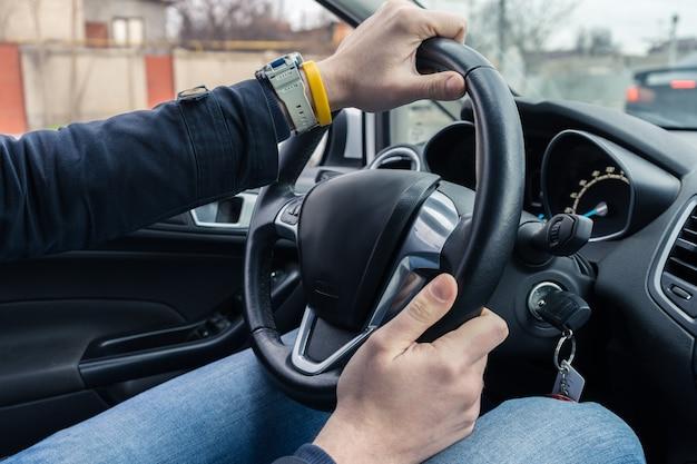 Uomo alla guida di un'auto moderna. la mano è sul volante. traffico cittadino sullo sfondo.
