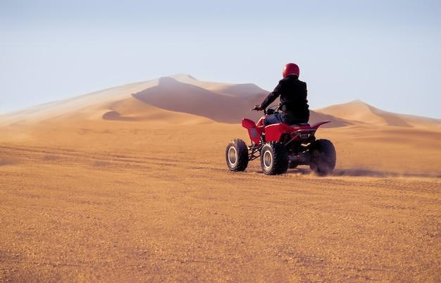 Uomo alla guida di quad nel deserto del namib in una giornata di sole