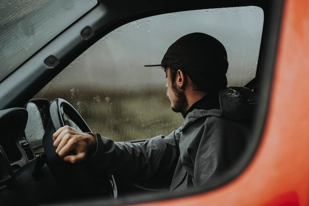Uomo alla guida di un furgone rosso mentre piove