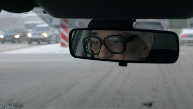 Uomo che guida nella città di inverno