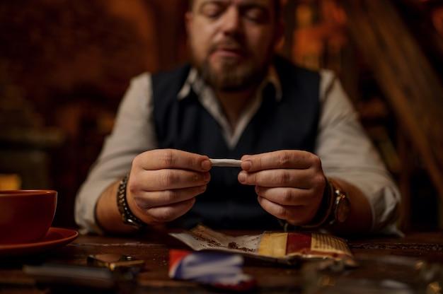 Uomo che sbava sigaretta arrotolata a mano, tavolo in legno sullo sfondo. cultura del fumo di tabacco, sapore ricco specifico. svaghi del fumatore maschio in ufficio