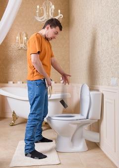 L'uomo fa cadere il cellulare nella toilette mentre fa pipì. interno del bagno di lusso