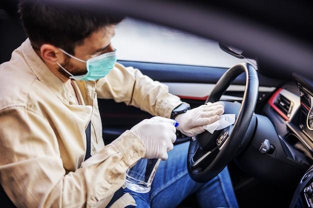 Uomo in tuta con maschera che disinfetta all'interno dell'auto, pulisce le superfici che vengono toccate frequentemente, previene l'infezione da virus covid-19, la contaminazione di germi o batteri.