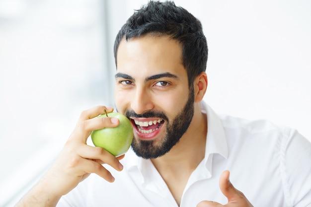 Uomo che mangia mela. bella ragazza con i denti bianchi che morde la mela. immagine ad alta risoluzione