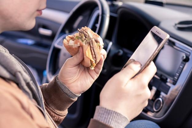 Uomo che mangia un hamburger e legge le notizie al telefono mentre è seduto in macchinasnack da asporto fast food per strada