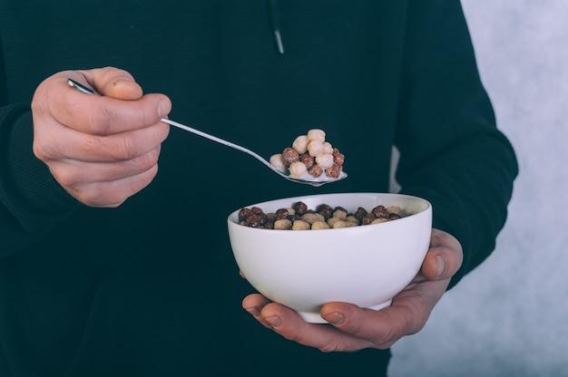 Un uomo che mangia cornflakes con latte su un legno.