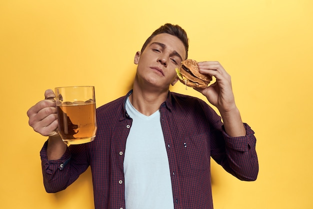 Uomo che mangia fast food mentre si tiene una brocca di birra