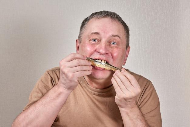 Uomo che mangia pesce fritto che tiene il pesce con le mani davanti al viso