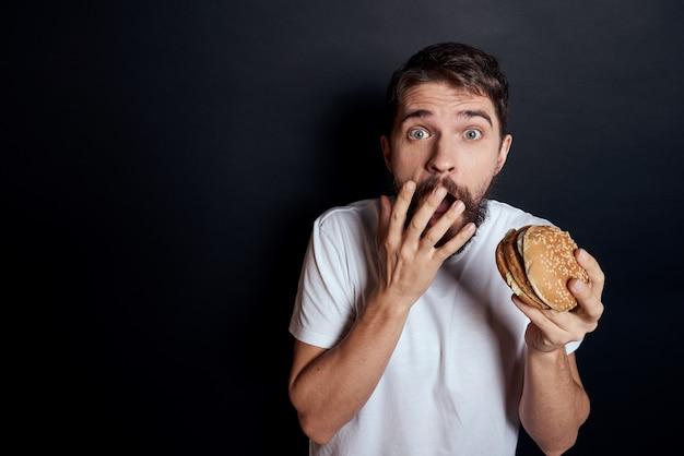 Uomo che mangia hamburger fast food