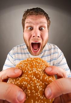 Uomo che mangia hamburger succoso