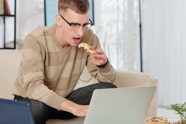 Uomo che mangia pizza e legge la posta elettronica