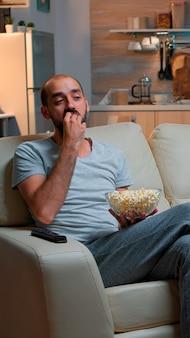 Uomo che mangia popcorn e guarda la tv, godendosi uno spuntino di mezzanotte