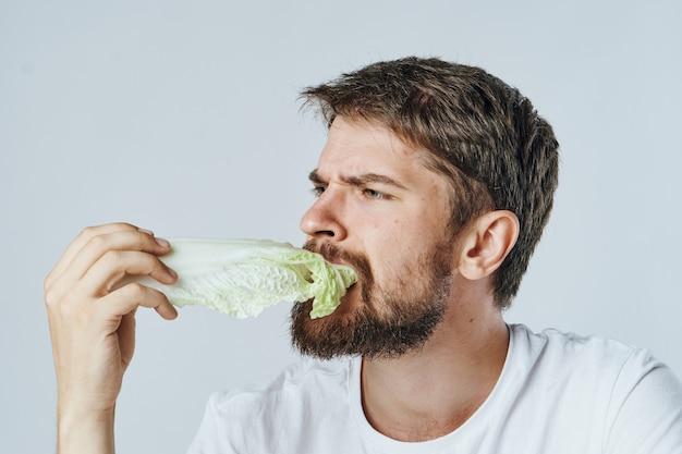Uomo che mangia le verdure crude foglia di cavolo stile di vita dieta vegetariana