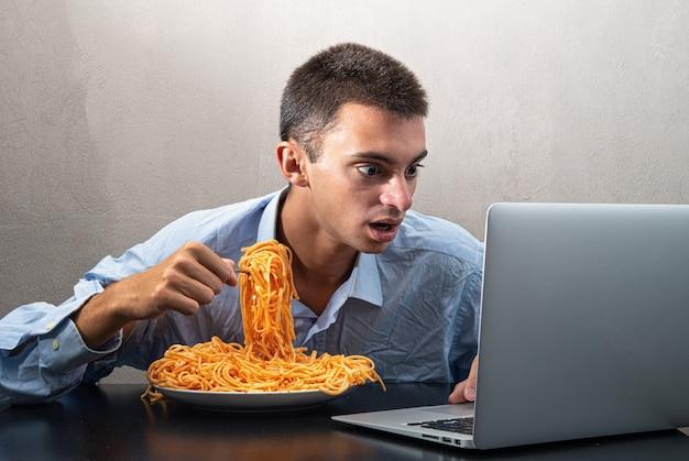 Uomo che mangia spaghetti con salsa di pomodoro e guarda il computer