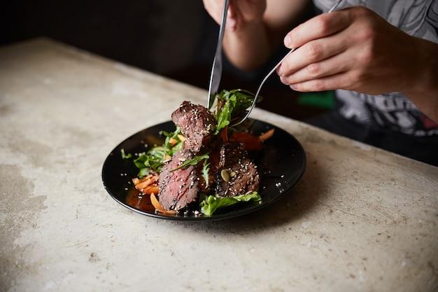 Uomo che mangia insalata di bistecca con manzo alla griglia; rucola; carota e semi. cibo salutare