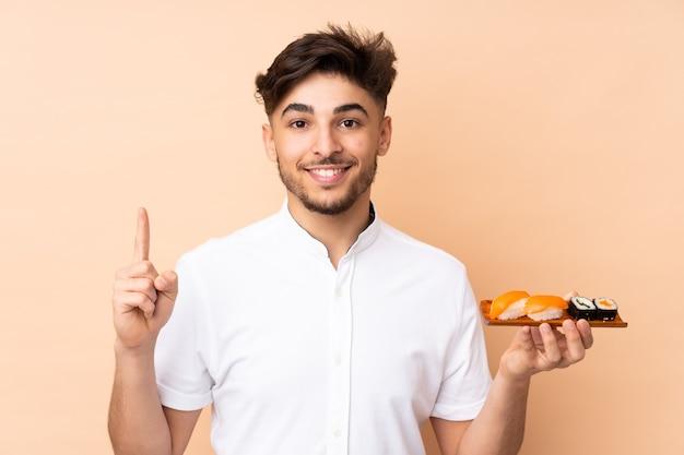 Uomo che mangia sushi isolato su beige rivolto verso l'alto una grande idea