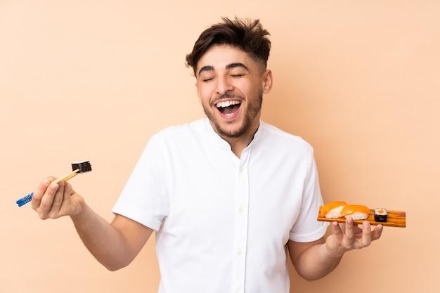 Uomo che mangia sushi isolato su beige