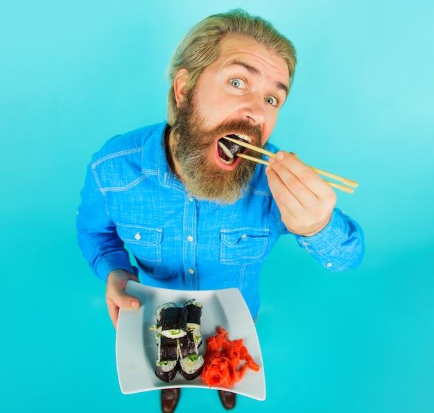 Uomo che mangia sushi. maschio con sushi sulle bacchette. consegna del sushi. ristorante di cucina giapponese.