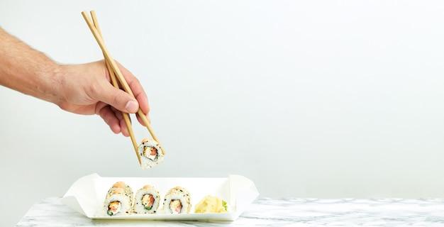 Uomo che mangia da asporto set di sushi giapponese, concetto di cibo di consegna