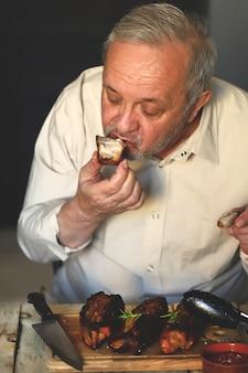 L'uomo mangia gustose costolette di maiale alla griglia