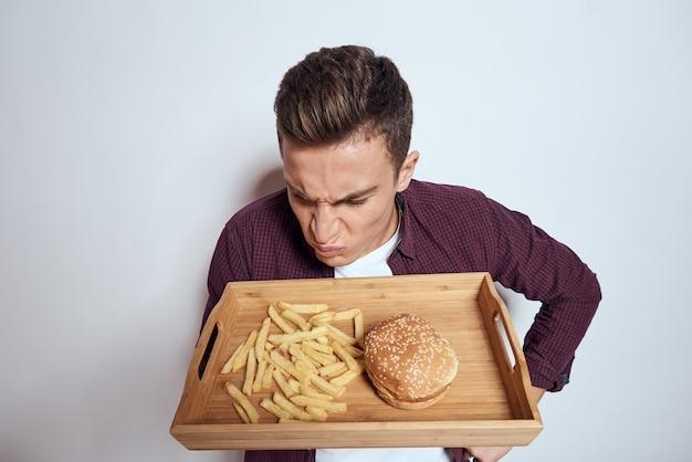 L'uomo mangia pallet di legno fast food patatine fritte hamburger dieta cibo ristorante sfondo chiaro