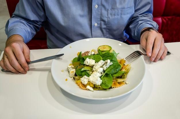 L'uomo mangia insalata mentre è seduto a un tavolo in un ristorante. le mani maschili si chiudono al tavolo