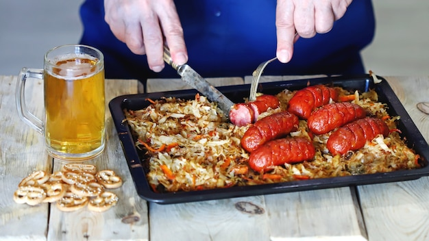 Un uomo mangia salsicce con crauti e birra.