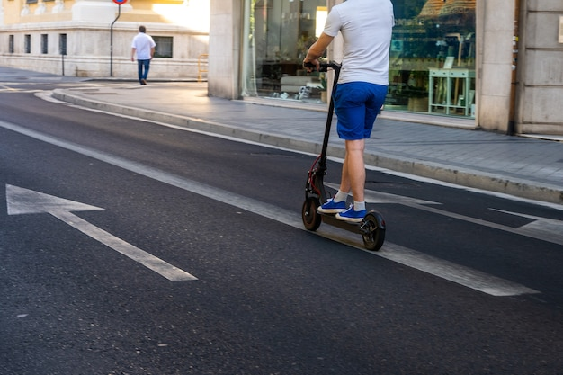 Uomo su uno scooter elettrico attraverso la città, copia spazio, mobilità urbana elettrica.