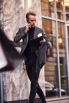 L'uomo in elegante abbigliamento formale con una tazza di bevanda e un blocco note in mano è fuori contro un edificio moderno e ha una conversazione al telefono.